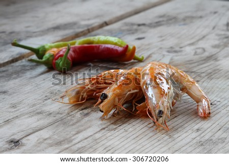 shrimp - prepared fresh seafood scampi on natural organic rustic wooden background - hot pepper - fresh red chili peppers in rastafari colors  on organic natural wooden rustic background - stock photo