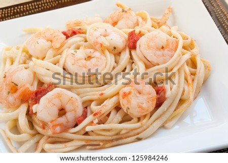 Shrimp scampi made with linguini, diced tomatoes, butter, garlic, parsley and herbs. Served on stacked white and brown plates. Shot in natural light. Selective focus with shallow definition of field. - stock photo