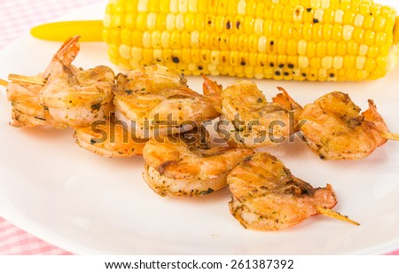 Shrimp seasoned in Old Bay mixture grilled on wooden skewers and served with roasted corn on the cob. - stock photo