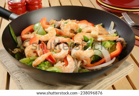 Shrimp stir fry in a wok with serving plates in the background - stock photo