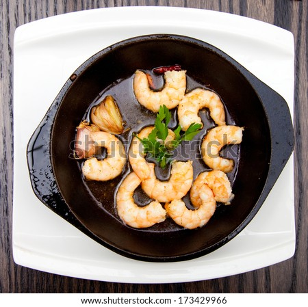 Shrimps and garlic in butter - stock photo