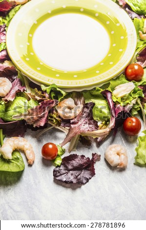 shrimps salad with lettuce and tomatoes and empty plate, close up - stock photo
