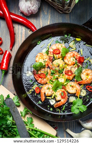 Shrimps served on a pan with chilli pepper - stock photo