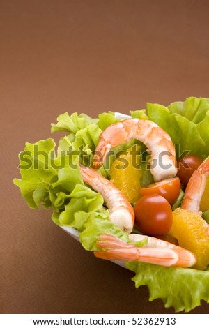 shrimps, tomato and lettuce on brown background