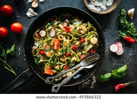 Shrimps with green tagliatelle served in the old pan
