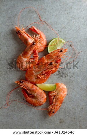 Shrimps with lime on stone background, selective focus - stock photo