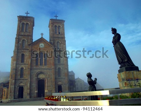 Shrine of Our Lady of La Salette in the French Alps on a foggy day with a view of sculptures in front of the church - stock photo