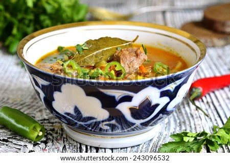 Shurpa - traditional uzbek soup from meat,potato and carrot with fresh herb. - stock photo