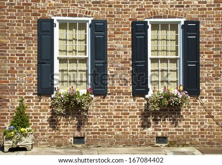 Shuttered windows decorated with flowers and plants in the brick wall of an eighteenth century house. - stock photo