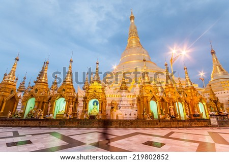Shwedagon Pagoda Temple shining in the beautiful sunset in Yangon, Myanmar. blur people scene - stock photo