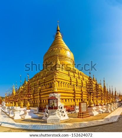 Shwezigon Pagoda in Nyaung-U,  Bagan, Burma. Enameled plaques in panels around the base illustrate previous lives of the Buddha. Clusters of zayats (rest houses) and shrines are around the pagoda. - stock photo