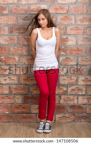 Shy girl casual design in red pants against a brick wall - stock photo