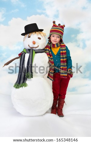 Shy little girl posing with her snowman