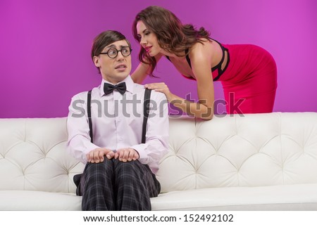 Shy nerd. Surprised nerd man sitting on the couch and looking at the beautiful young woman standing close to him - stock photo