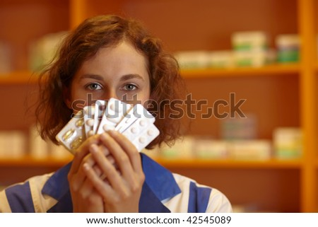 Shy pharmacist holding many pills in hand - stock photo