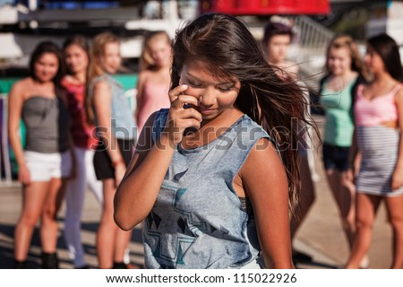 Shy teenage Filipino girl looking down with friends nearby - stock photo
