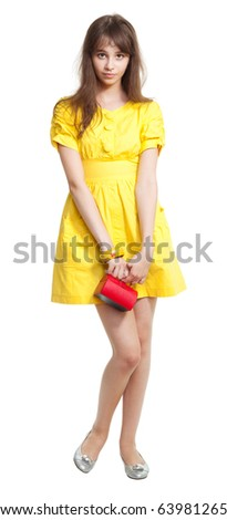 Shy teenage girl in yellow with small vivid red purse - stock photo