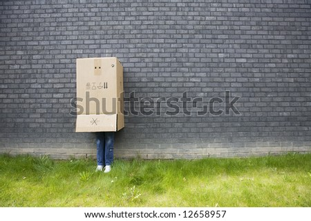 shy teenage girl standing against a wall with a cardboard box over his head - stock photo