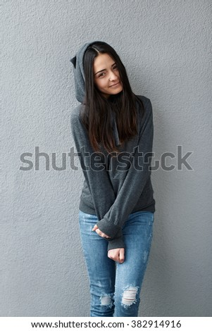 shy teenager girl clutching her hands to her stomach - stock photo