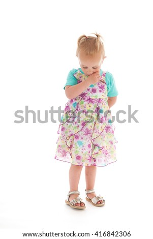 Shy toddler girl standing in studio in summer dress isolated over white background