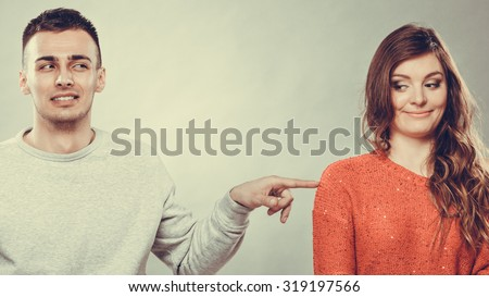Shy woman and man sitting on sofa couch next each other. First date. Attractive girl and handsome guy meeting dating and trying to talk. Male touching picking up female. Instagram filtered. - stock photo