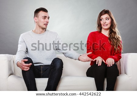 Shy woman and man sitting on sofa couch next each other. First date. Attractive girl and handsome guy meeting dating and trying to talk. Male offering a hand to female.