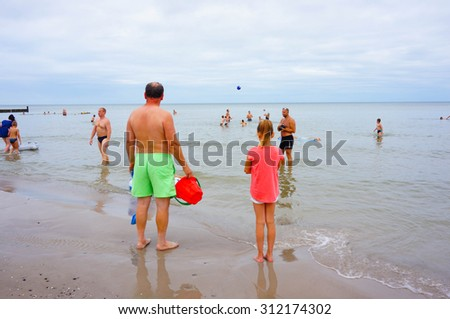 SIANOZETY, POLAND - JULY 21, 2015: People standing in the water of a beach