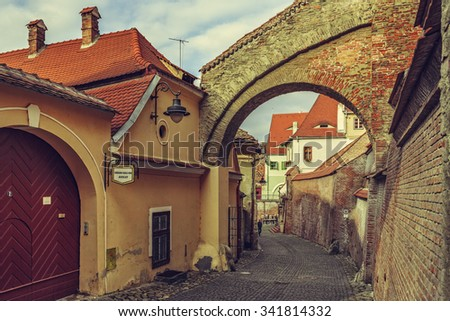 SIBIU, ROMANIA - 12 NOVEMBER, 2015: Peaceful street view with cobblestone backstreets, old fortified brick arcades and walls in the historic center of Sibiu city, European Capital of Culture in 2007. - stock photo