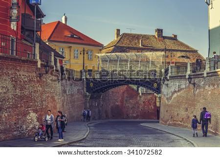 SIBIU, ROMANIA - 13 NOVEMBER, 2015: Tourists stroll along the sideways under the Bridge of Lies, built in 1859, the first wrought iron bridge in Romania. - stock photo