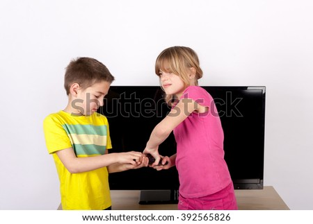 Sibling arguing over the remote control in front of the TV. - stock photo