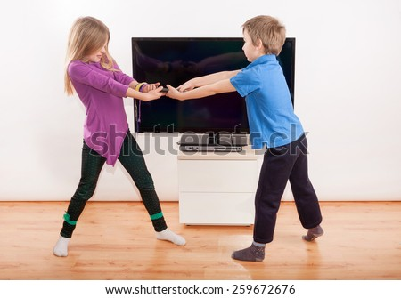 Sibling fighting over the remote control in front of the TV - stock photo