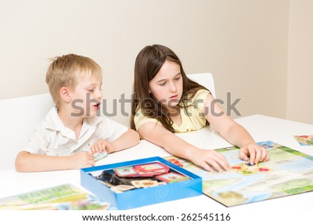 Siblings, a boy and girl play a board game on a white table against a white background - stock photo