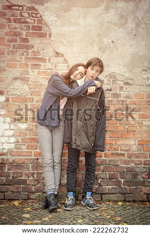 siblings arm in arm in front of an old brick wall - stock photo
