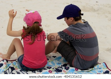 Siblings (brother and sister) sitting on a breach in a state park in Florida - stock photo