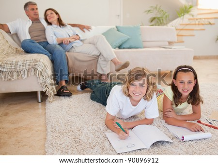 Siblings doing their homework on the carpet with parents behind them - stock photo