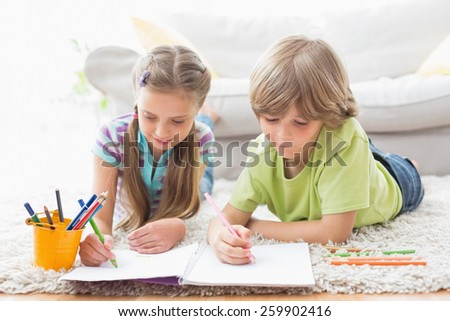 Siblings drawing with colored pencils while lying on rug at home in the living room - stock photo