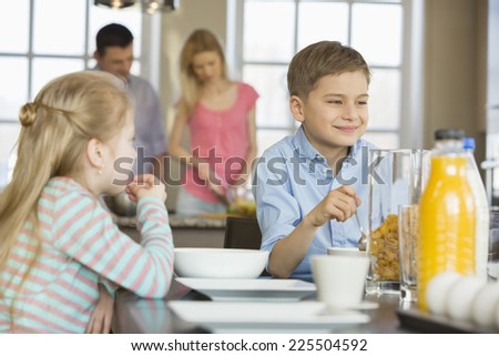 Siblings having breakfast at table with parents cooking in background - stock photo