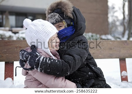 siblings hugging on a winter day - stock photo