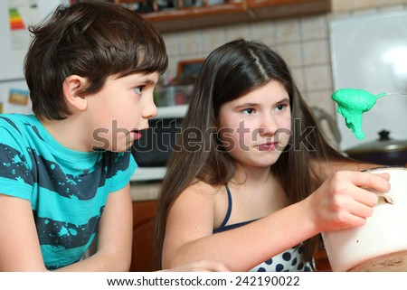 siblings in the kitchen cooking cake - stock photo