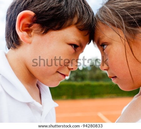 Siblings rivalry - two kids at the tennis court looking competitive - stock photo