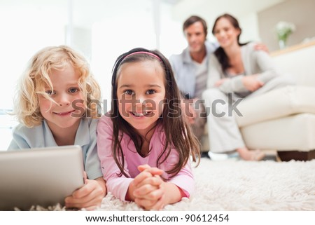 Siblings using a tablet computer while their parents are in the background in a living room - stock photo