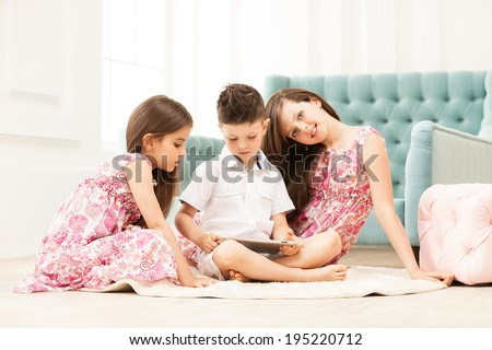 Siblings using tablet while sitting on the floor at home - stock photo