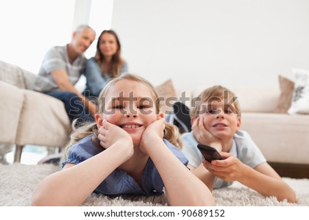Siblings watching television with their parents on the background in a living room - stock photo