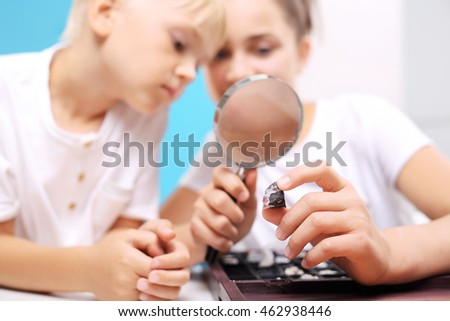 Siblings watching through a magnifying glass rock. Two children, a girl and a boy watching through a magnifying glass stones from his collection of rocks.
