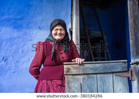 SIC, ROMANIA -  JUNE, 2014: In this hungarian village the traditions are well preserved. This elderly woman wearing a traditional costume is showing her house, at June, 2014, in Sic (Szek), Romania