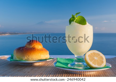 Sicilian lemon granita and a typical warm brioche with blue sea and Mount etna in the background