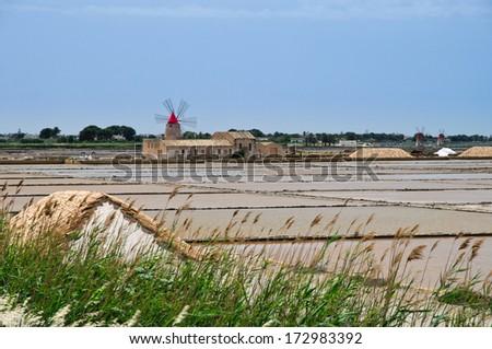Sicilian Salt Ponds and Mill in Trapani, Marsala, Sicily  - stock photo