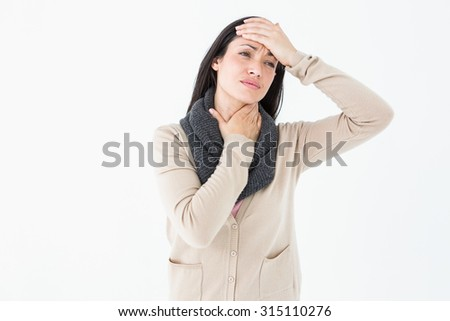 Sick brunette touching her throat and her head on white background - stock photo