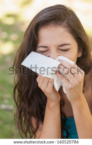 Sick brunette woman using a handkerchief sitting in a park