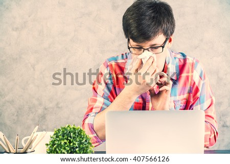 Sick caucasian male with handkerchief looking at laptop on concrete wall background - stock photo